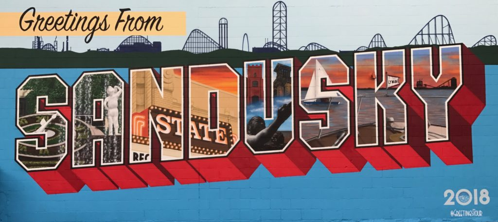 The Greetings from Sandusky mural finished in 2017 on Sandusky State Theatre features Washington Park's Floral Clock and Boy with the Boot sculpture, the lighted marquee of the historic theater, Sandusky's role in the Underground Railroad, and Sandusky Bay and the Sandusky Coal Docks at dusk in a view from a Lyman boat. (City of Sandusky)