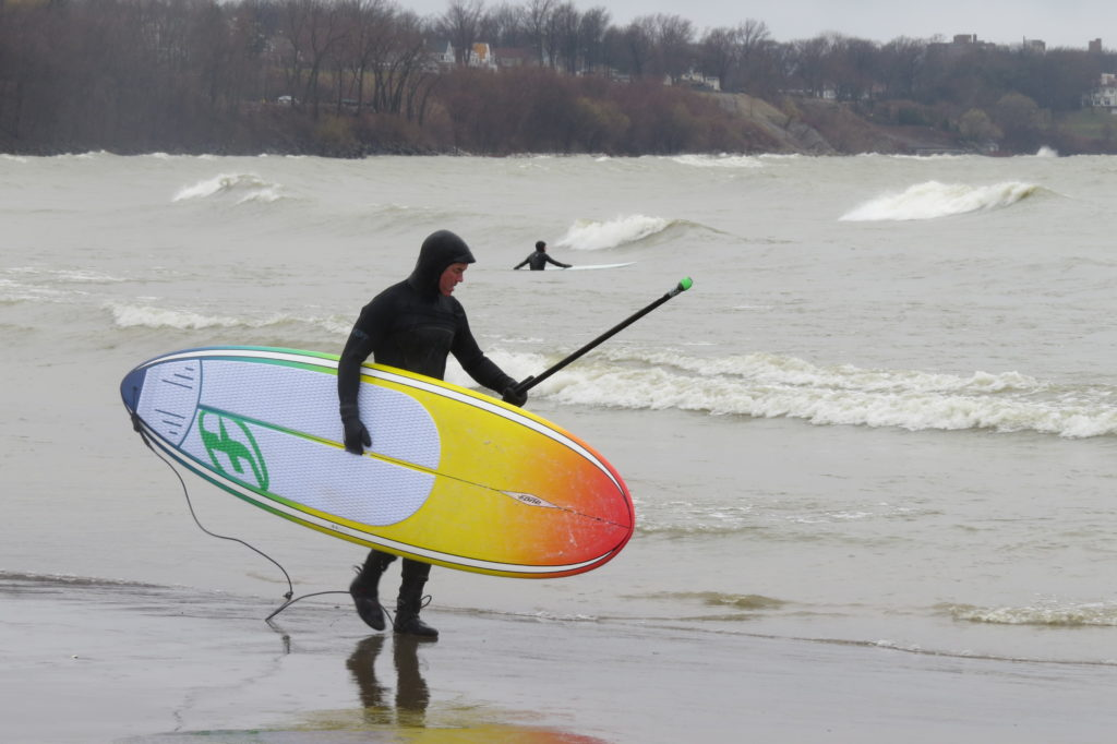 Brian Willse walks across Edgewater Beach, ready to catch another wave on April 15, 2018. (Laura Johnston, RocktheLake)