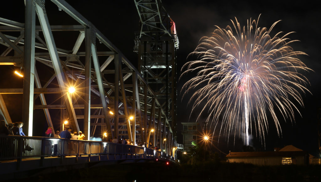 Crowds of people watch the 2015 July 4th fireworks show from the River Rd. Bridge, also known as the Whiskey Island Bridge, on the west bank, as the fireworks explode over the mouth of the Cuyahoga River.(Chuck Crow, The Plain Dealer)