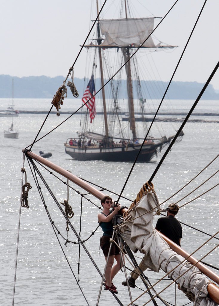 Mariah Clark, left, works with a fellow crewman on the head rig of the US Brig Niagara as the Lynx, a square topsail schooner out of Newport Beach, California, makes her final run of the Tall Ships Festival at the Port of Cleveland, Sunday, July 7, 2013, in Cleveland. (Peggy Turbett, The Plain Dealer)