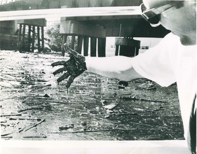 Sludge drips off the fingers of Plain Dealer reporter Richard Eller  after he dipped  his hand in the polluted Cuyahoga River in Cleveland Ohio, in an undated photo taken sometime in the 1960s.  Scanned from e-mail June 10, 2009. CB. Michael Scott  (Plain Dealer file photo by Marvin M. Greene,   MARVIN M. GREENE  PLAIN DEALER FILE PHOTOGRAPH  Former reporter Richard Ellers says he didn't appreciate the thickness of the pollution on the Cuyahoga River until he dipped his hand into it and it came out black and gooey. The photo was taken in the 1960s. The Plain Dealer