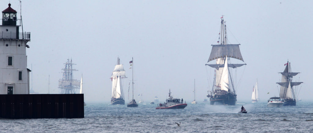 The Parade of Tall Ships, greeted by small pleasure craft, passes the lighthouse at the mouth of the Cuyahoga River on Wed. July 3, 2013.  A dozen ships featured in the Port of Cleveland 2013 Tall Ships Festival. (Thomas Ondrey, The Plain Dealer)
